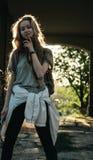 La fille de l'adolescence se tient dans la voûte au coucher du soleil Silhouette d'une fille avec de longs cheveux image stock