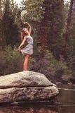 La fille de l'adolescence se tient sur la grande roche étirant des bras Image stock