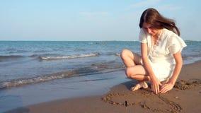La fille de l'adolescence seule dessine un coeur dans le sable banque de vidéos