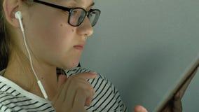 La fille de l'adolescence utilise le comprimé avec des écouteurs Temps de soir?e clips vidéos