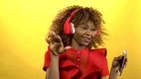 La fille de l'aspect d'afro-américain dans des écouteurs chante des chansons Fond jaune banque de vidéos
