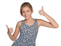 La fille de la préadolescence tient ses pouces  Photographie stock