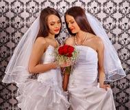 La fille de lesbiennes de mariage dans la robe nuptiale garde des fleurs Image libre de droits