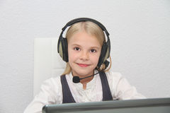 La fille de Llittle s'assied devant un ordinateur portable avec des écouteurs et apprend Image stock
