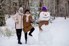 La fille de mère et d'adulte sculptent un grand vrai bonhomme de neige images stock