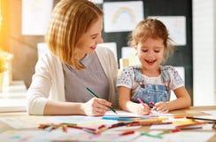 La fille de mère et d'enfant dessine dans la créativité dans le jardin d'enfants Photographie stock libre de droits