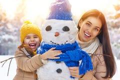 La fille de mère et d'enfant un hiver marchent Image stock