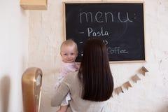 La fille de maman et d'enfant en bas âge jouant la planification de menu écrivent au blackboa photos stock