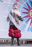 La fille de Maslenitsa-the dans une écharpe nationale chante au festival Images stock