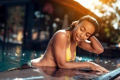 La fille de mulâtre dans un bikini pose sur l'appareil-photo dans la piscine Images libres de droits