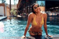 La fille de mulâtre dans un bikini pose sur l'appareil-photo dans la piscine Image stock