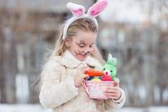 La fille de Pâques avec le panier d'oeufs et le lapin drôle font face à l'expression à la forêt Photographie stock