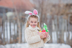 La fille de Pâques avec le panier d'oeufs et le lapin drôle font face à l'expression à la forêt Image stock
