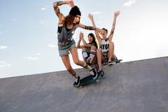 La fille de patineur monte sur la planche à roulettes au parc de patin Image stock
