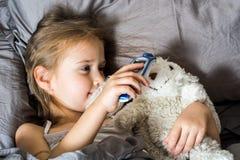 La fille de petit enfant mesure la température d'un Ther de non contact photos stock