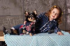 La fille de petit enfant se trouve avec le chien noir de chuhuahua Images stock