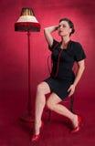 La fille de pin-up dans la robe noire pose séduisant Photo libre de droits