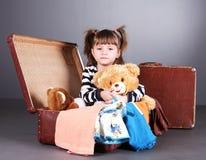 La fille de quatre ans s'assied joyeux dans une vieille valise Photographie stock