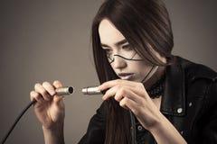 La fille de robot de Cyberpunk relie deux câbles électriques Images libres de droits