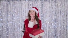 La fille de Santa avec un cadeau dans des ses mains montre son doigt plus tranquillement Fond de Bokeh clips vidéos