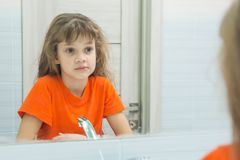 La fille de sept ans regarde elle-même dans le miroir, dans la salle de bains image libre de droits