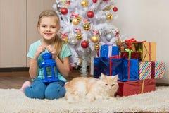 La fille de sept ans s'assied avec un chat sous l'arbre de Noël avec des cadeaux et sourire heureusement Photos libres de droits