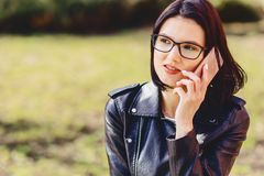 La fille de sourire attirante en verres parle par le téléphone photographie stock