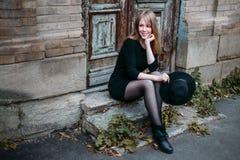 La fille de sourire blonde avec de longs cheveux, dans la robe noire avec un chapeau dans des ses mains, s'assied sur les étapes  image stock