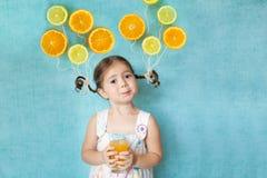 La fille de sourire boit du jus d'orange frais Photos stock