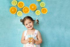 La fille de sourire boit du jus d'orange frais Photo libre de droits
