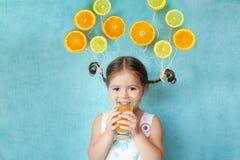 La fille de sourire boit du jus d'orange frais Photographie stock libre de droits