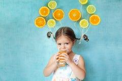 La fille de sourire boit du jus d'orange frais Images libres de droits