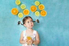 La fille de sourire boit du jus d'orange frais Photographie stock