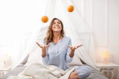 La fille de sourire de brune dans le pyjama bleu-clair s'assied sur le lit et les jets d'auvent oranges sur la feuille grise avec photographie stock