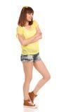La fille de sourire dans les shorts de jeans et le dessus jaune regarde loin Photos libres de droits