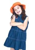 La fille de sourire dans un denim s'habillent et chapeau orange image libre de droits