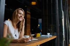 La fille de sourire de charme de hippie a reçu de bonnes actualités au téléphone de cellules tandis qu'elle s'asseyant dans le ca Photographie stock