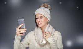 La fille de sourire en hiver vêtx examiner le smartphone image libre de droits