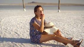 La fille de sourire heureuse appréciant le coucher du soleil, mangeant la pastèque, s'asseyent sur le sel, piliers clips vidéos
