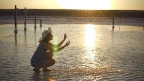 La fille de sourire heureuse appréciant le soleil, arrose l'eau salée du lac dans les rayons du coucher du soleil banque de vidéos