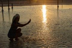 La fille de sourire heureuse appréciant le soleil, arrose l'eau salée du lac dans les rayons du coucher du soleil photo libre de droits