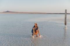 La fille de sourire heureuse appréciant le soleil, arrose l'eau salée du lac dans les rayons du coucher du soleil photos stock