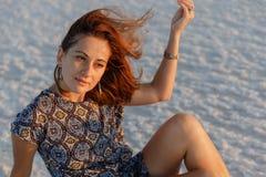 La fille de sourire heureuse appréciant le soleil de coucher du soleil et secoue sa tête, se repose sur le sel photographie stock