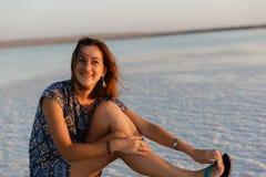 La fille de sourire heureuse appréciant le soleil de coucher du soleil et secoue sa tête, se repose sur le sel image libre de droits