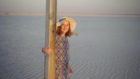 La fille de sourire heureuse appréciant le soleil, danse et rires, réclame vous avec le geste clips vidéos