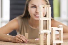 La fille de sourire joue avec les briques en bois Photo stock