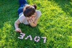 La fille de sourire met l'amour de mot des bourgeons roses sur l'herbe verte Images stock