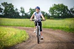 La fille de sourire montent sur le vélo sur le paysage rural photographie stock libre de droits