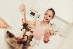 La fille de sourire prépare une salade à la cuisine images libres de droits