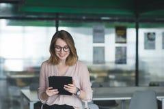 La fille de sourire regarde le comprimé et les sourires le fond du bureau Une fille avec une tablette est dans le bureau photo libre de droits